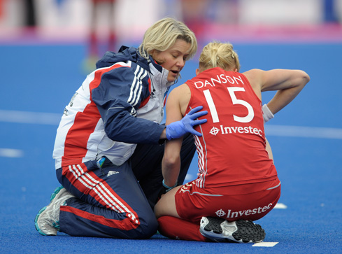 QEHB physiotherapist Emma Batchelor attends to Alex Danson during a GB women's hockey match. Photograph: Ady Kerry/GB Hockey.